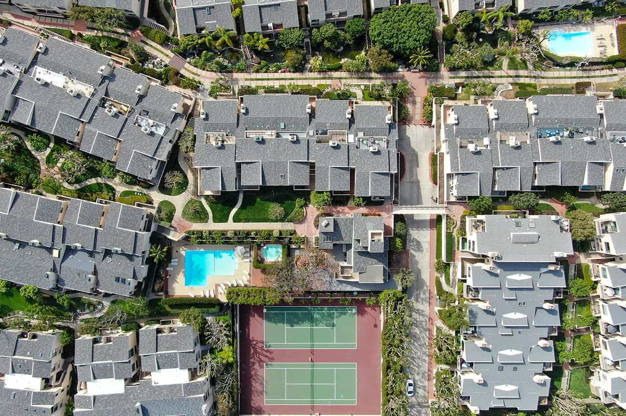 Aerial View Of Condo Community With Tennis Court And Pool In Sol