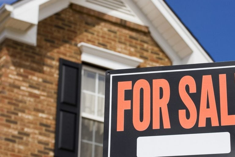 for sale sign in front of brick house