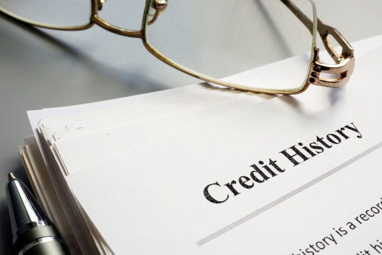 """paper titled """"credit history"""" with glasses laying on top"""