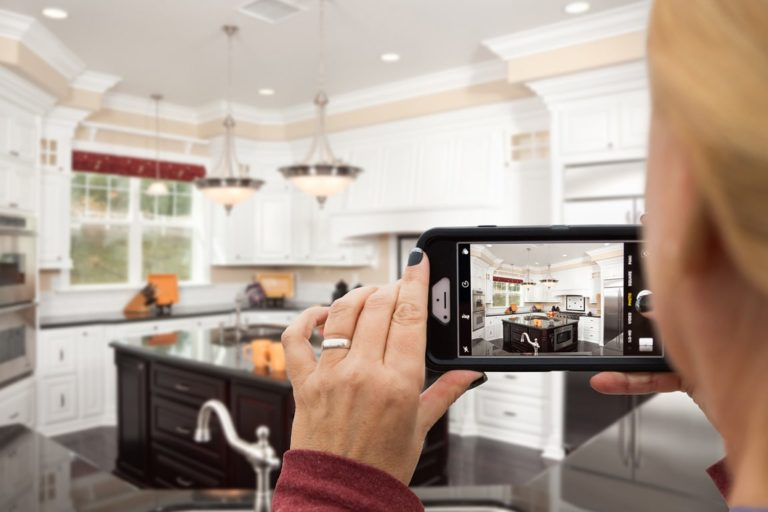 woman taking picture of kitchen on mobile phone
