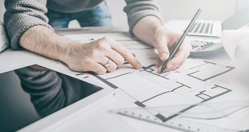 man drawing home plans