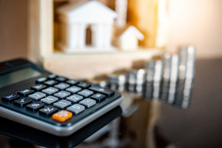 calculator on table with coin stacks in background
