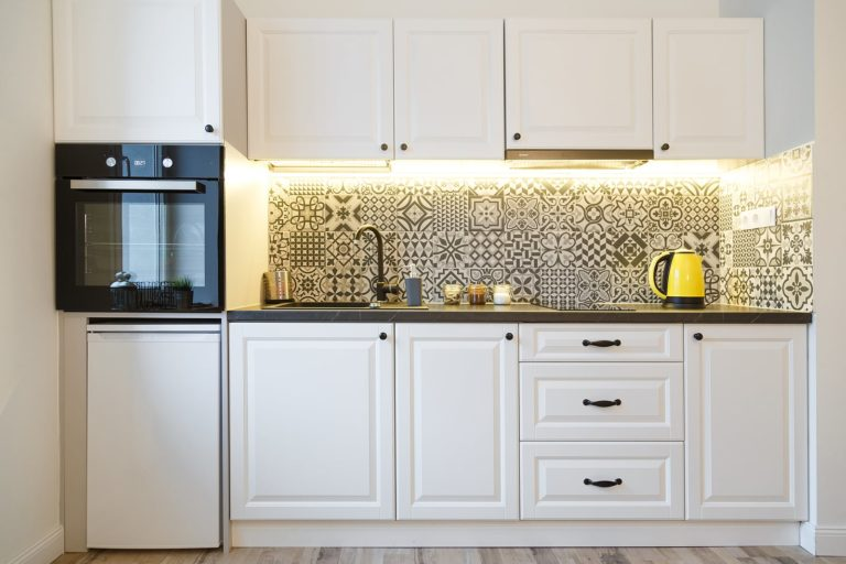 white kitchen cabinets with bold print backsplash and yellow appliances