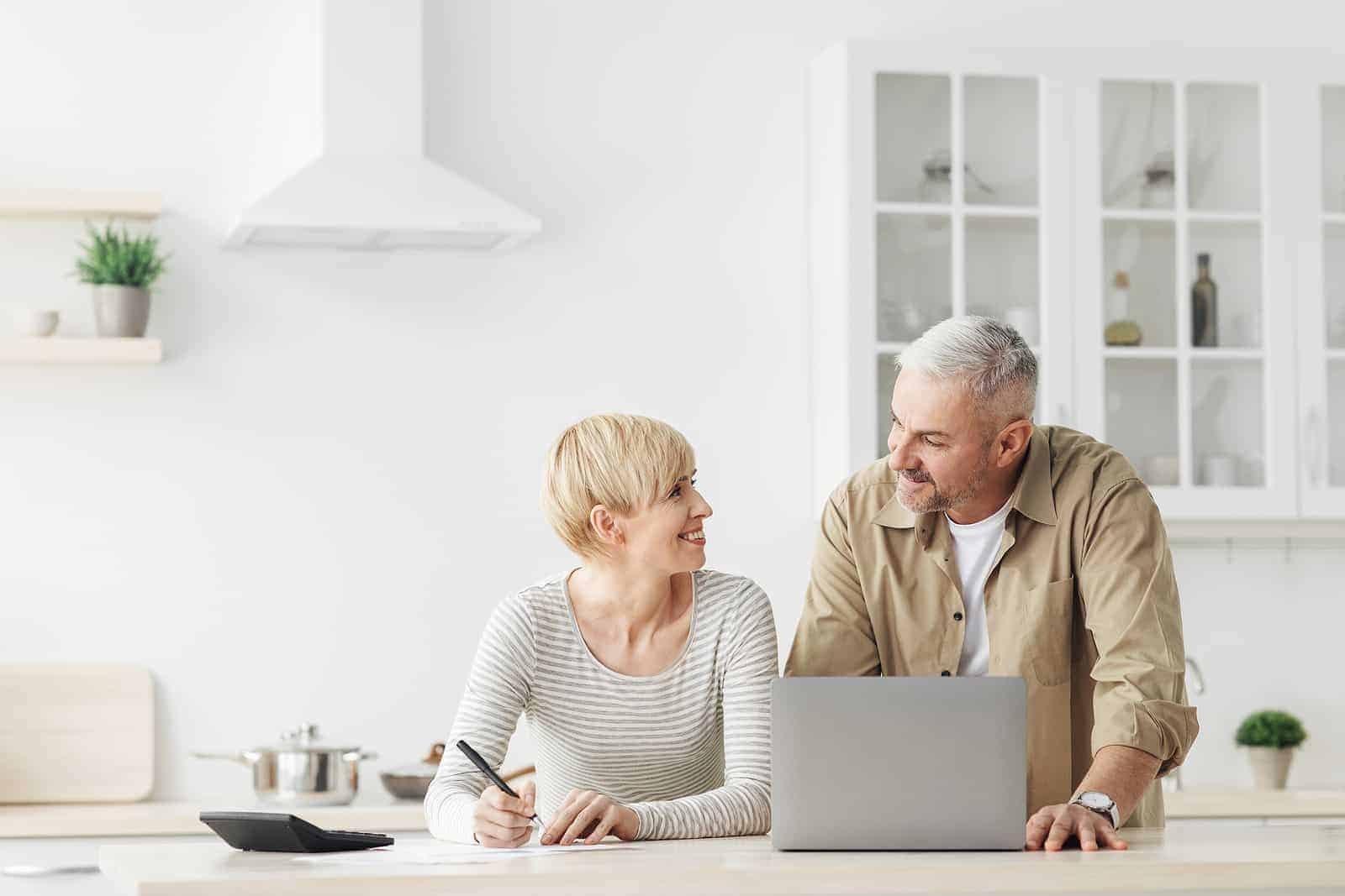 smiling couple in home on laptop