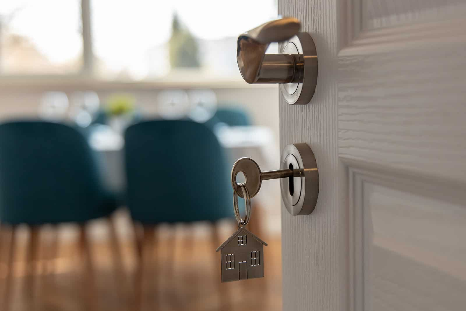 key in door with metal house keychain