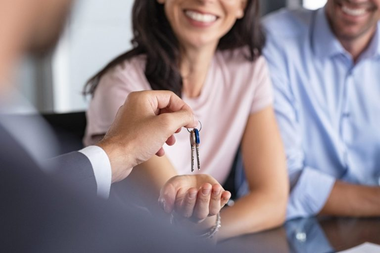 Close up of man hand giving house keys to woman