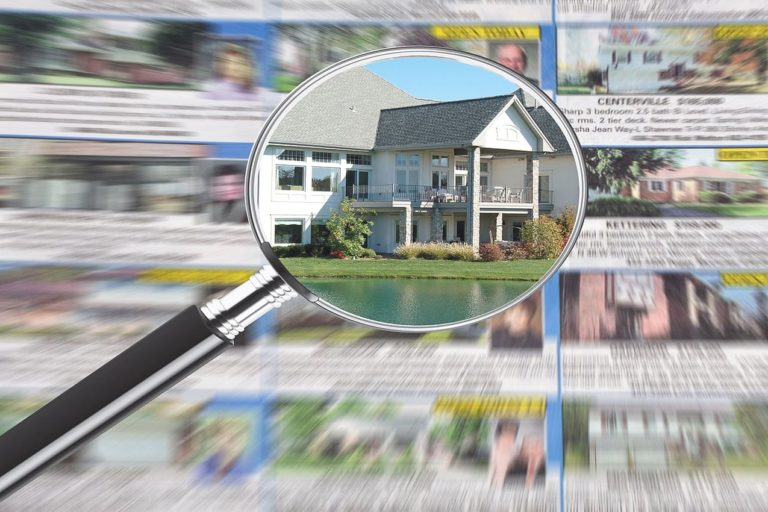 magnifying glass over newspaper debunking real estate myths