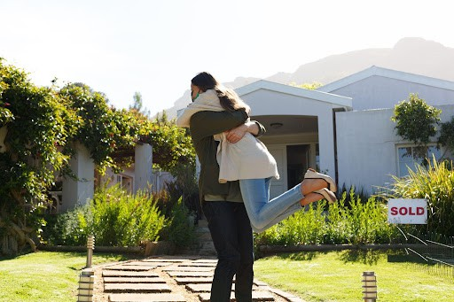 woman and man hugging in front of new home