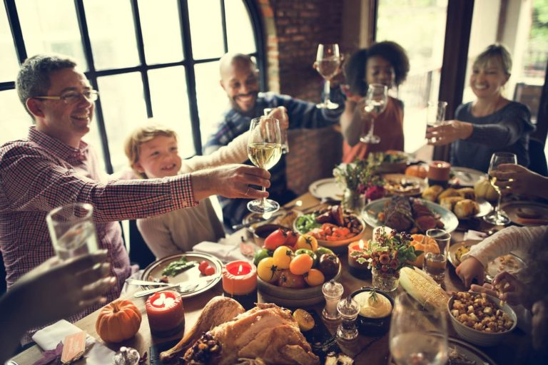 people around table for thanksgiving smiling, toasting each other with wine glasses in hand