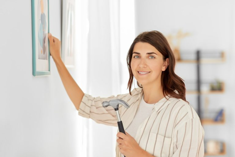 woman hanging a picture on the wall with hammer in hand