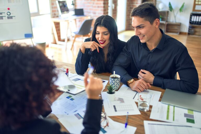 young couple reviewing finances with an advisor
